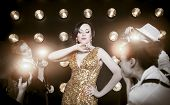 picture of superstars  - Superstar woman wearing golden shining dress posing to paparazzi - JPG
