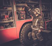 stock photo of fireman  - Fireman taking equipment from firefighting truck  - JPG