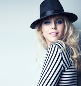 stock photo of top-hat  - Young attractive blonde woman wearing hat and stripy top fashion concept - JPG