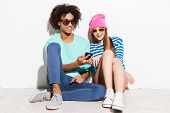 foto of funky  - Funky young couple smiling and looking at the mobile phone while sitting against white background - JPG