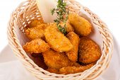 picture of high calorie foods  - Crispy fried crumbed chicken nuggets in a wicker basket served as a finger food or appetizer with a creamy dip in a bowl alongside - JPG