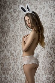 stock photo of erotic  - pretty girl in erotic pose in glamour ester shoot with fluffy bunny ears and tail lace panties and naked perfect body turned on her back - JPG