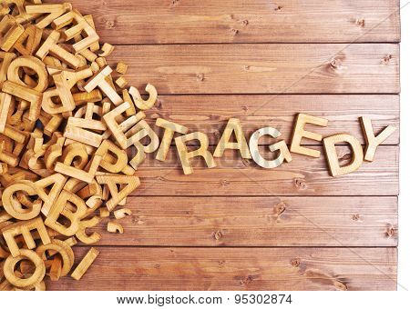 Word tragedy made with wooden letters