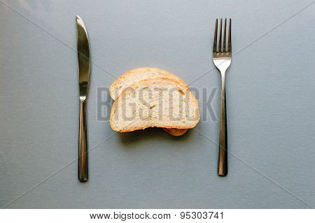 Fresh bread lies on gray table between fork and knife