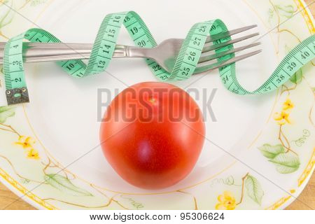 Measuring Tape And A Fork With Tomato Isolated