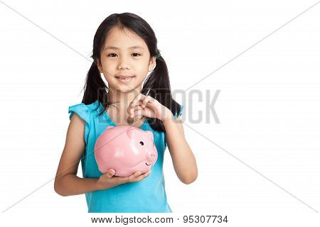 Little Asian Girl  With A Coin And Piggy Bank