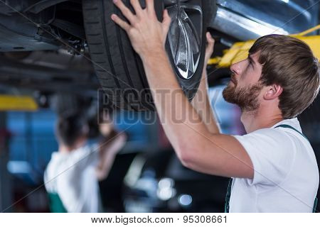 Automobile Mechanics Repairing A Car