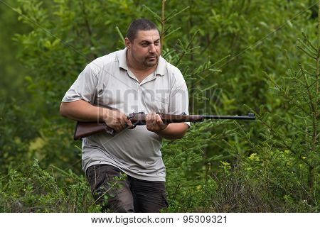Hunter Sneaking With Rifle In Hands