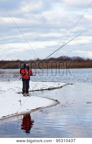 Fisherman Standing On The River With Fishing Rod