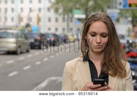 Young Woman Reading A Text Message On Her Mobile