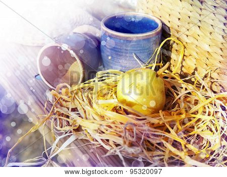 Blue ceramic cup, pear and hay on a wooden table with sunshine. Autumn background