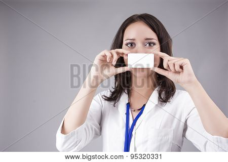 Young Medical Female Doctor Presenting And Showing White Card In Front Of Mouth For Product Or Text.