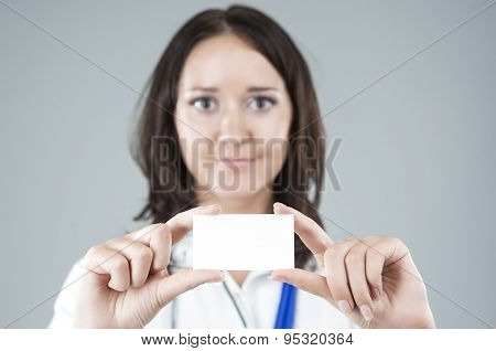 Portrait Of Medical Female Doctor Presenting And Showing White Card For Product Or Text. Caucasian M