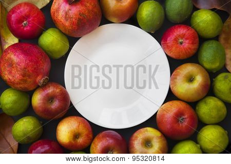 Autumn background with Red apples, pomegranate, limes on black d