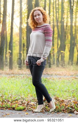 Curly Beautiful Woman Poses In Autumn Park At Sunny Evening