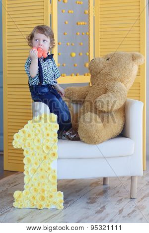Little Handsome Happy Boy Stands On Soft Armchair With Big Bear Toy