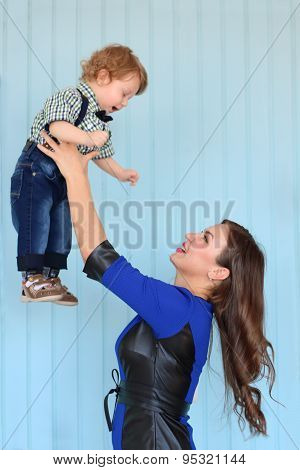 Beautiful Woman In Blue Dress Throws Up Little Son In Light Blue Room