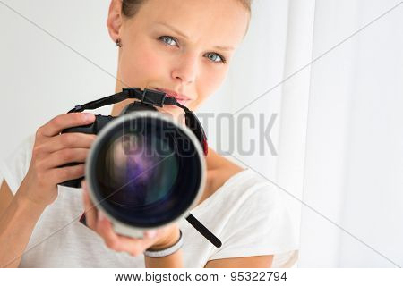 Pretty, female photographer with digital camera - DSLR and a huge telephoto lens (color toned image; shallow DOF)