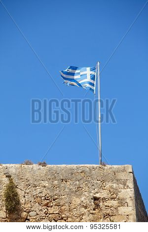 Waving flag of Greece on a  medieval fortress in Crete against clear blue sky