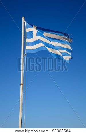 Waving flag of Greece on a pole against clear blue sky