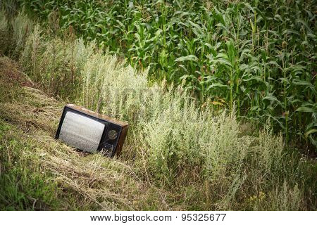 Old broken TV in the field with white noise on screen
