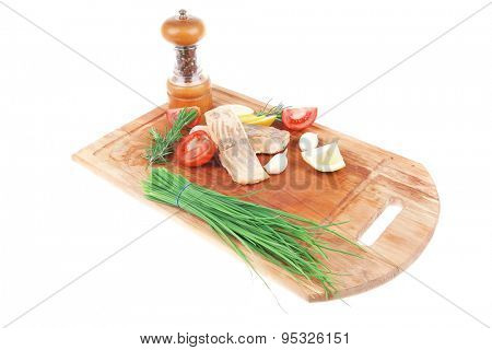 healthy fish cuisine : baked pink salmon steaks with green onion, cherry tomatoes, small pepper grinder, rosemary twigs and lemon on wooden board isolated on white background