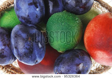 mix of fresh raw ripe juice fruits apple plum peach and lemon in basket isolated over white background