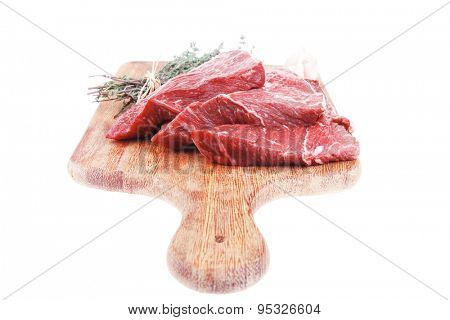 raw beef meat fillet with peppercorn and thyme ready to grill on wood figured aged board isolated over white background