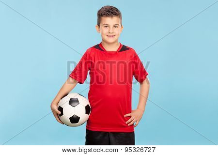 Little boy in a red jersey holding a football and looking at the camera on blue background