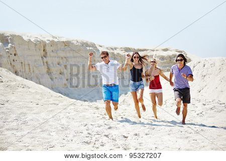 Happy friends running down sandy beach on hot day