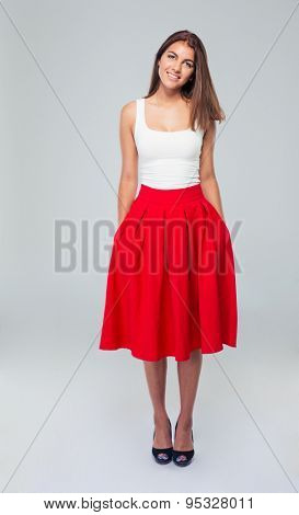 Full length portrait of attractive smiling woman in skirt posing over gray background and looking at camera