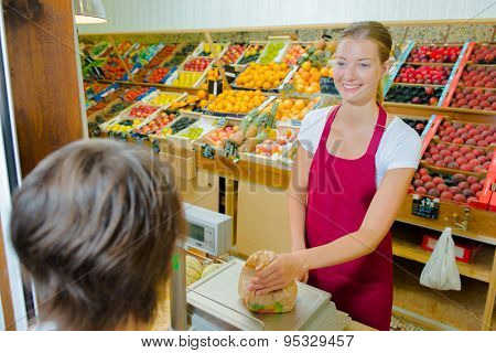 Shop assistant weighing fruit