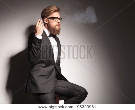 Side view of a blond business man resting on a stool while enjoying a cigarette.