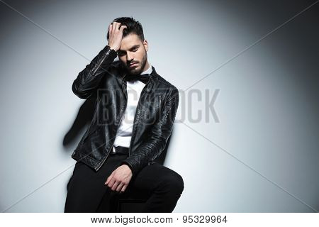Picture of a handsome business man fixing his hair while sitting on a stool.