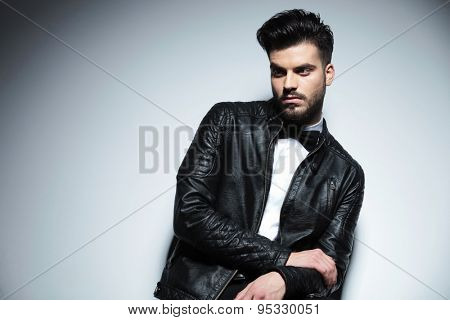 Portrait of a handsome business man looking away from the camera, on grey studio background.