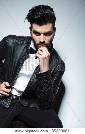 Attractive young business man holding his hand to the chin, thinking while sitting on a stool.