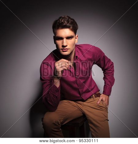 Casual man holding one hand in his pocket while sitting on a stool.