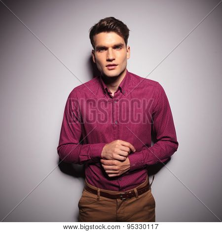 Handsome young man fixing his sleeve while leaning on a wall.