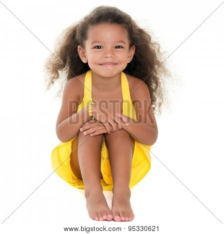 Cute small african-american or hispanic girl sitting on the floor isolated on white