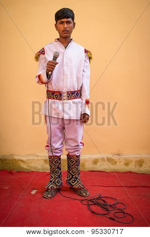 GODWAR REGION, INDIA - 15 FEBRUARY 2015: Young Indian musician dressed in wedding ceremony outfit holds microphone. Marriages in India are filled with ritual and celebration that last for days.
