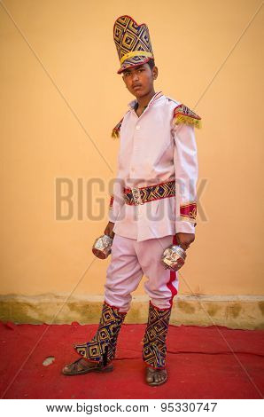 GODWAR REGION, INDIA - 15 FEBRUARY 2015: Young Indian musician dressed in wedding ceremony outfit holds instrument. Marriages in India are filled with ritual and celebration that last for days.
