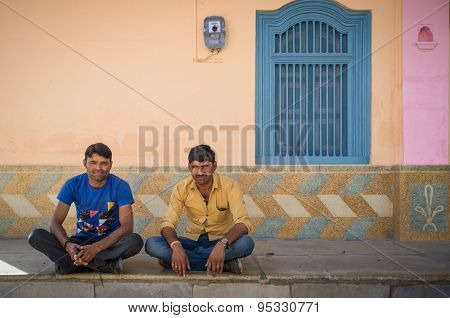 GODWAR REGION, INDIA - 15 FEBRUARY 2015: Two typical modern Indian men sit cross-legged on ground in front of home.