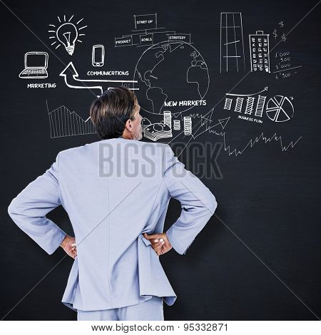 Serious businessman with hands on hips against blackboard