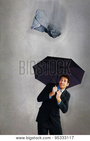 Businessman sheltering with black umbrella against grey room