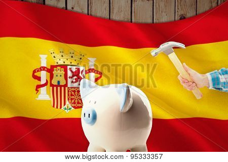 hand holding hammer against digitally generated spanish national flag