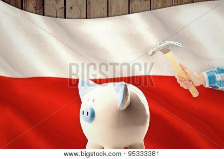hand holding hammer against digitally generated polish flag rippling