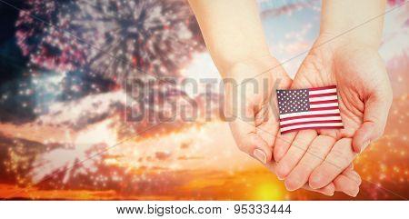 Hands presenting against colourful fireworks exploding on black background