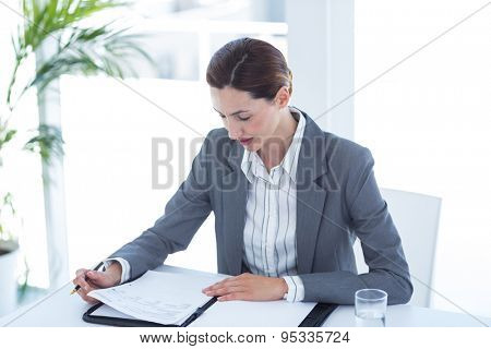 Businesswoman reading file in an office