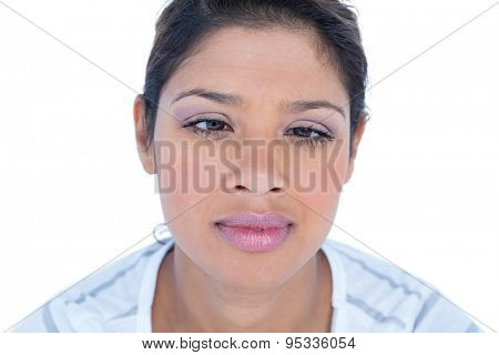 Pretty brunette grimacing at camera on white background