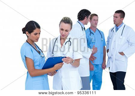 Doctor and nurse discussing over notes on a white background